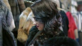Блестящая женщина смотря на меховой шыбе в магазине сток-видео