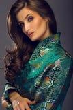 Блестящая молодая женщина в зеленой куртке японского стиля смотря Стоковые Изображения RF