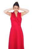 Блестящая молодая модель в красном платье покрывая ее уши Стоковые Фото