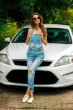 Блестящее брюнет представляя около белого автомобиля Стоковое фото RF