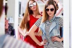 Блестящие девушки пробуя на солнечных очках представляя перед зеркалом в магазине модной одежды Стоковое фото RF