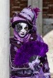 Блестящий совершитель женщины с фиолетовым костюмом и венецианская маска во время масленицы Венеции Стоковое Изображение