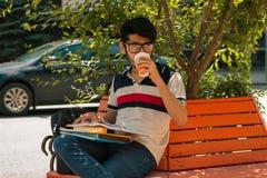 Блестящий студент сидя на кофе стенда выпивая и держа книгу Стоковое Изображение