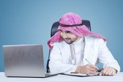 Ближневосточный доктор смотря компьтер-книжку Стоковое Фото