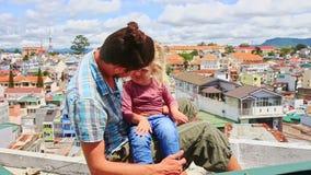 Близкая маленькая девочка отца сидит на высокой крыше дома против города видеоматериал