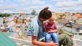 Близкая маленькая девочка отца сидит на высокой крыше дома против города сток-видео