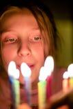 Близкий взгляд на ребенке смотря на свечах на именнином пироге стоковые изображения