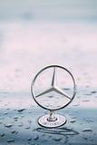 Близкий взгляд логотипа звезды металла Benz Мерседес на влажном клобуке b Стоковая Фотография