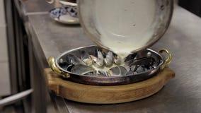 Близкий снимок кашевара блюда подготавливает мидий испеченных в сковороде сток-видео