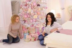 2 близкого друга делят приятные эмоции и праздничные подарки, сидят Стоковое Изображение
