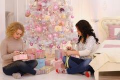 2 близкого друга делят приятные эмоции и праздничные подарки, сидят Стоковые Фото