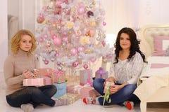 2 близкого друга делят приятные эмоции и праздничные подарки, сидят Стоковые Изображения