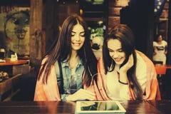 2 близкого друга наблюдая что-то на таблетке Стоковая Фотография RF