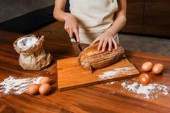 Близкое изображение рук режа свежий хлеб стоковое изображение rf