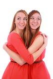 2 близнеца девушек в красный обнимать платьев Стоковые Изображения