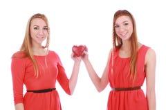 2 близнеца девушек в красных платьях с подарком Стоковое Фото