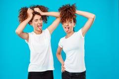 2 близнеца девушек держа волосы, шутя над голубой предпосылкой Стоковая Фотография RF