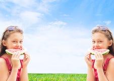 2 близнеца девушек есть арбуз Стоковое Изображение RF