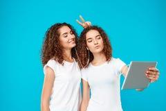 2 близнеца девушек делая selfie на таблетке над голубой предпосылкой Стоковые Изображения