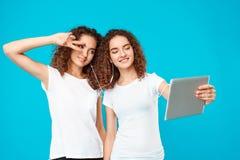2 близнеца девушек делая selfie на таблетке над голубой предпосылкой Стоковое Изображение