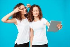 2 близнеца девушек делая selfie на таблетке над голубой предпосылкой Стоковые Фото