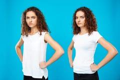 2 близнеца девушек представляя с оружиями подбоченясь над голубой предпосылкой Стоковые Фото