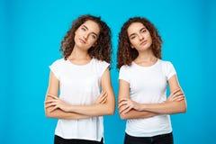 2 близнеца девушек представляя с пересеченными оружиями над голубой предпосылкой Стоковые Изображения