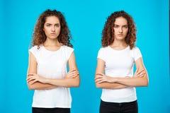 2 близнеца девушек представляя с пересеченными оружиями над голубой предпосылкой Стоковое Фото