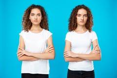 2 близнеца девушек представляя с пересеченными оружиями над голубой предпосылкой Стоковые Изображения RF