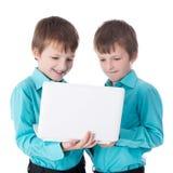 2 близнеца мальчиков используя компьтер-книжку на белизне Стоковое Изображение