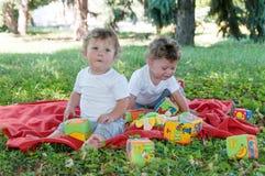 2 близнеца мальчиков сидя на красном одеяле с игрушками Стоковое фото RF
