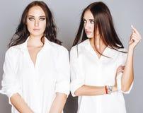 2 близнеца представлять сестер, делая selfie фото, одели такую же белую рубашку, разнообразные друзей стиля причёсок Стоковая Фотография