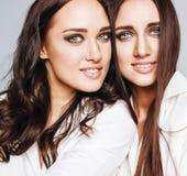 2 близнеца представлять сестер, делая selfie фото, одели такую же белую рубашку, разнообразные друзей стиля причёсок Стоковые Фото