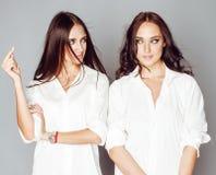 2 близнеца представлять сестер, делая selfie фото, одели такую же белую рубашку, разнообразные друзей стиля причёсок, людей образ Стоковое Фото