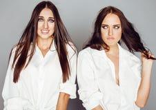 2 близнеца представлять сестер, делая selfie фото, одели такую же белую рубашку, разнообразные друзей стиля причёсок Стоковая Фотография RF