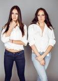 2 близнеца представлять сестер, делая selfie фото, одели такую же белую рубашку, разнообразные друзей стиля причёсок Стоковые Изображения