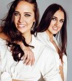 2 близнеца представлять сестер, делая selfie фото, одели такую же белую рубашку, разнообразные друзей стиля причёсок Стоковые Фотографии RF