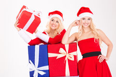 2 близнеца сестер в костюмах Санта Клауса с подарками Стоковые Фотографии RF