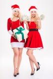 2 близнеца сестер в платьях и шляпах Санта Клауса Стоковые Фотографии RF