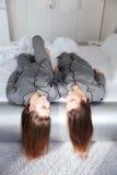 2 близнеца сестер в серых пижамах лежа на кровати Стоковые Изображения RF