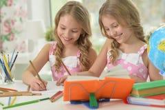 2 близнеца сестер делая домашнюю работу Стоковое Фото
