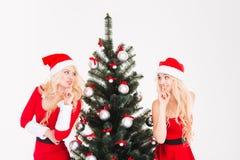 2 близнеца сестер показывая безмолвие подписывают стоящую близко рождественскую елку Стоковое Изображение RF