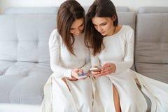 2 близнеца сестер сидя на кресле и используя мобильные телефоны Стоковые Изображения