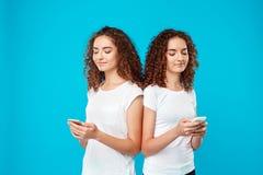 2 близнеца усмехаться девушек, смотря телефоны над голубой предпосылкой Стоковое Фото