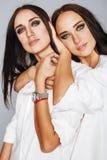 2 близнеца эмоциональный представлять сестер, делая selfie фото, одели такую же белую рубашку, разнообразный стиль причёсок, ярки Стоковые Фото