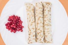 Блинчики и ягоды красной смородины на большой белой плите Стоковые Фотографии RF