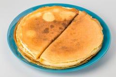 Блинчики на голубой предпосылке белизны плиты Стоковое Фото