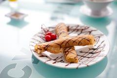 Блинчики с вареньем вишни на белой плите, которая стоит на стеклянном столе около окна в внутреннем уютном кафе отмело стоковая фотография