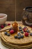 Блинчики с свежими ягодами и ложкой меда на деревянном конце предпосылки вверх Стоковое Фото