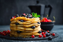 Блинчики с свежими ягодами и сиропом клена на темной предпосылке Стоковое Изображение RF